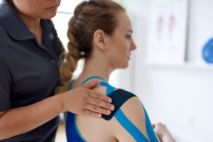 Physiotherapist applying tape to a hypermobile shoulder